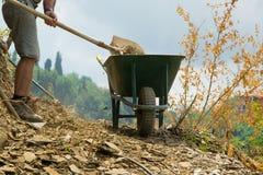 De gewassenmening van de jonge mens met schop beweegt stenen van de weg stock foto