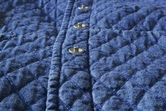 De gewatteerde textuur van het de doekelement van het stoffendenim dicht omhoog met metaalknopen stock afbeeldingen