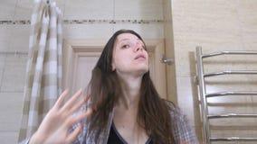 De gewekte vermoeide vrouw in de badkamers smakt zich op de wangen om te ontwaken stock video