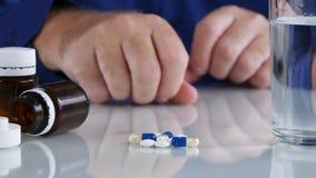 De gewijde persoon met handen het schudden neemt medische pillen en drugs van lijst stock footage