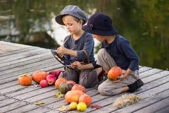 De gewone kinderen schilderen kleine Halloween-pompoenen Royalty-vrije Stock Foto's