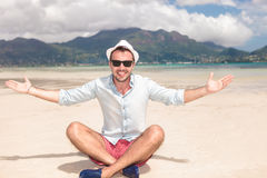 De gezette gelukkige jonge mens nodigt u aan het strand uit Stock Afbeelding