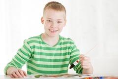 De gezette glimlachende jongen houdt borstel in hand stock foto's