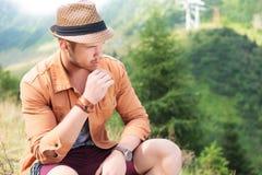 De gezette toevallige mens houdt een stro in zijn mond, openlucht Royalty-vrije Stock Foto