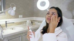 De gezichtshuidzorg, schitterend meisje gebruikt een bevochtigende gezichtsroom liggend op de laag in schoonheidssalon stock video