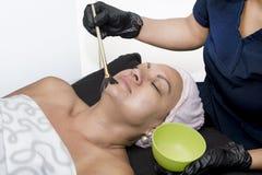 De gezichtstoepassing van het Schilmasker op Gezicht royalty-vrije stock afbeelding