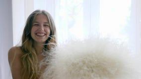 De gezonde dame vrij van allergieën met boeket van veergrassen gelukkig kijkt in camera op achtergrond van venster stock video