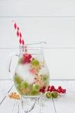 De gezonde detoxbes goot op smaak gebracht water De zomer die eigengemaakte drank met kruisbessen en wit en rode aalbes op wit ve Stock Fotografie