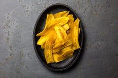 De gezonde Eigengemaakte Spaanders van de banaanweegbree op zwarte plaat, leiachtergrond royalty-vrije stock fotografie