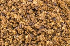 De gezonde graangewassen van granolamuesli met chocoladeachtergrond Royalty-vrije Stock Foto's