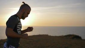 De gezonde levensstijl, jonge atleet gaat binnen voor openluchtsporten op aard tegen zonsondergang stock footage