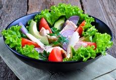 De gezonde salade van avocado, tomaten, blikte tonijn, uien en sla met parmezaanse kaas, peterselie en olijfolie in Royalty-vrije Stock Foto's