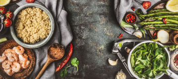 De gezonde saladevoorbereiding met het koken lepelt en superfood ingrediënten: quinoa, asperge, verse seasong, kruiden en garnale Stock Afbeelding