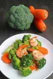 De gezonde schotel van garnaal beweegt gebraden die met broccoli en wortel op witte plaat worden gediend stock afbeeldingen