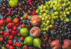 De gezonde verscheidenheid van het de zomerfruit Zwarte en groene druiven, aardbeien, fig., zoete kersen, perziken Stock Foto's
