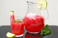 De gezonde verse smoothiedrank van rode watermeloen, de kalk, de munt en het ijs drijven af stock foto's