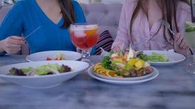 De gezonde voeding, jonge vrouwen tijdens een diner deelt zitting bij lijst en het eten van Griekse salade in koffie mee stock footage