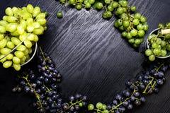 De gezonde vruchten blauwe en groene donkere druiven van wijndruiven, bos van wijndruiven op de houten lijst klaar te eten royalty-vrije stock afbeelding