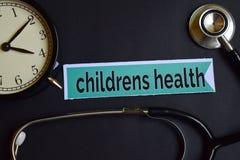 De Gezondheid van kinderen op het drukdocument met de Inspiratie van het Gezondheidszorgconcept wekker, Zwarte stethoscoop stock afbeeldingen