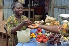 De Ghanese marktvrouw verkoopt groenten en kruiden Stock Foto
