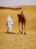 De gids van de kameel met kameel in de woestijn stock afbeeldingen