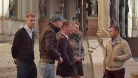 De gids vertelt iets de toeristengroep, maakt één toerist foto stock footage