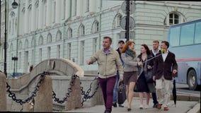 De gids vertelt iets de toeristengroep op achtergrond van oude cityscape stock video