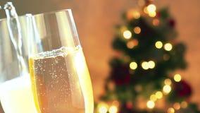De gietende champagne in fluiten met gouden bellen met gouden samenvatting die vage Kerstboom knipperen steekt bokeh aan stock footage