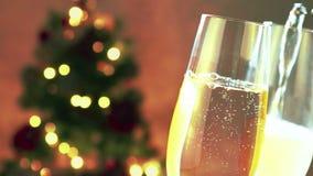 De gietende champagne in fluiten met gouden bellen met gouden samenvatting die vage Kerstboom knipperen steekt bokeh aan stock video