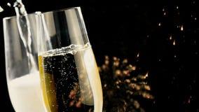 De gietende champagne in fluiten met gouden bellen met gouden samenvatting schittert het vuurwerk van fonkelingslichten op zwarte stock videobeelden