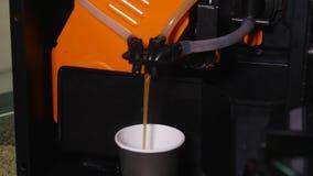 De gietende koffie van de koffiemachine binnen aan de document kop stock footage