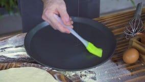 De gietende olijfolie van de chef-kokkok op het bakken van dienblad en het uitspreiden met borstel op keukenlijst Olijfolie voor  stock video