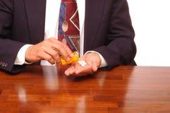 De Gietende Pillen van Buinessman in hand Stock Foto's