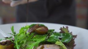 De gietende saus van de chef-kokkok aan plantaardige salade dicht omhoog Kok die salade met saus voorbereidt Het voedsel van de p stock video