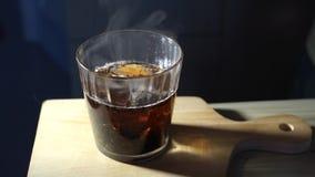 De gietende suiker in een glas gebrouwen thee en beweegt omhoog het stock video
