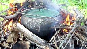 De gietijzerketel voor het koken kan op een open brand worden gebruikt stock footage