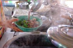De gietlepel wordt afgevoerd in een kom van noedels, die noedel in Thai koken royalty-vrije stock afbeeldingen