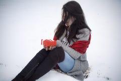 De gift en de zitting van de vrouwenholding op sneeuw Royalty-vrije Stock Foto's