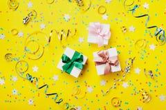 De gift of het huidige vakje verfraaide kleurrijke confettien, ster, suikergoed en wimpel op de gele mening van de lijstbovenkant royalty-vrije stock afbeeldingen