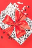 De gift met rode satijnboog met schittert decoratieve harten op een rode achtergrond Feestelijk concept royalty-vrije stock fotografie