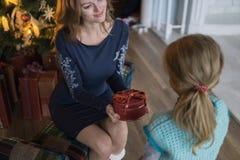 De gift van de dochter van mamma bij de Kerstboom royalty-vrije stock afbeeldingen