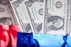 De gift van Kerstmis met dollars op rode achtergrond Royalty-vrije Stock Afbeeldingen