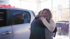 De gift van de moederdag, aantrekkelijke man geeft auto aan vrouw die gelukkig omhels en toont sleutels bij het autohandel drijve stock videobeelden