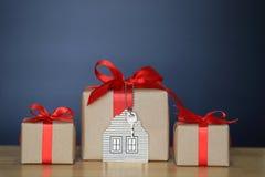 De giftdoos met rood lint en het huis modelleren met sleutels op zwarte achtergrond, Gift nieuw huis en Onroerende goederenconcep stock foto's