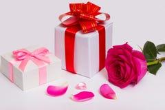 De giftdozen met bogen, rode linten, namen en bloemblaadjes toe stock foto