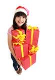 De giften die van de de vrouwenholding van Kerstmis de hoed van de Kerstman dragen Royalty-vrije Stock Afbeeldingen