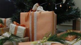 De giften stelt dozen onder verfraaide Kerstmisspar met voor speelgoed en witte lichte het knipogen slinger De beweging van de di stock video