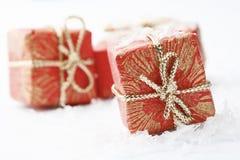 De giften van Kerstmis met het rode verpakken en bogen. Stock Afbeelding