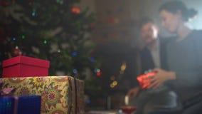 De giften van paaruitwisselingen dichtbij een verfraaide Kerstboom stock videobeelden