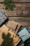 De giften van verpakkingskerstmis in uitstekend beige blauw broodjesdocument op oud houten bureau Hoogste mening Vlak leg De ruim royalty-vrije stock foto